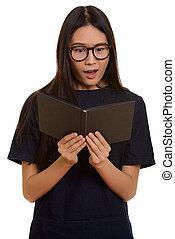 Young beautiful Asian teenage girl reading book while...