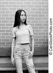 Young beautiful Asian teenage girl standing while thinking against brick wall
