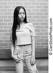 Young beautiful Asian teenage girl standing while thinking and looking down against brick wall