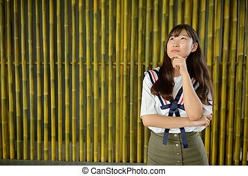 Young beautiful Asian teenage girl thinking against bamboo fence