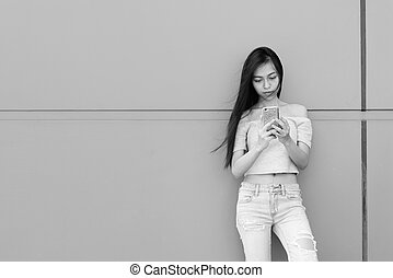 Young beautiful Asian teenage girl using mobile phone while standing and leaning against concrete wall outdoors