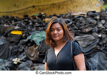 Young beautiful Asian tourist woman backpacker in dirty alley