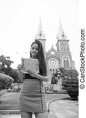 Young beautiful Asian tourist woman looking at the map against view of cathedral