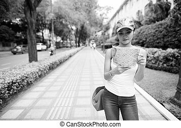 Young beautiful Asian tourist woman looking at the map in the city streets
