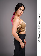 Young beautiful Asian woman against gray background
