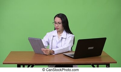 Young beautiful Asian woman doctor multi-tasking