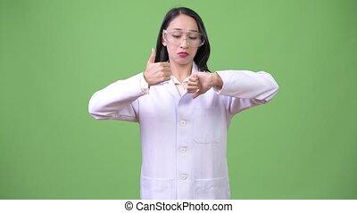 Young beautiful Asian woman doctor wearing protective...