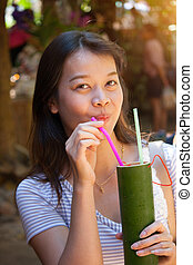 Young beautiful asian woman drinking  Roselle juice in a cup made of bamboo