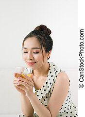 Young beautiful asian woman enjoying a cup of tea while sitting at home