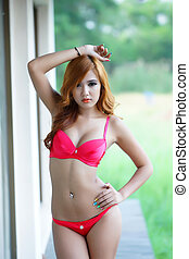Young beautiful Asian woman in lingerie voluptuous posing outdoors.
