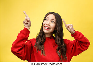 Young beautiful asian woman pointing to copyspace, isolated on yellow background