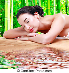 Young beautiful asian woman relaxing at spa salon in bamboo forest