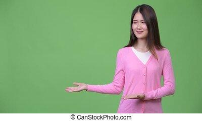 Young beautiful Asian woman showing something