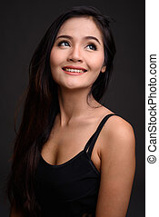 Young beautiful Asian woman smiling against gray background