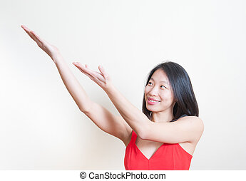Young beautiful asian woman smiling pointing out white backgroun