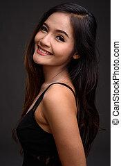 Young beautiful Asian woman smiling