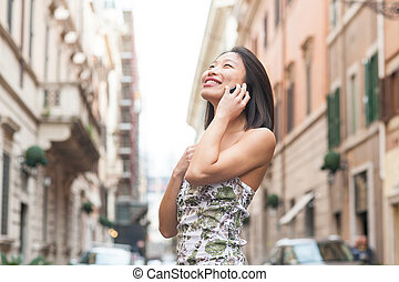 Young beautiful asian woman smiling using mobile phone spring ur