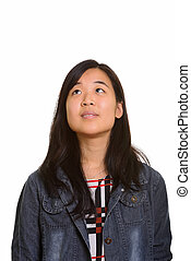 Young beautiful Asian woman thinking and looking up
