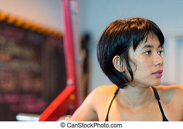Young beautiful Asian woman thinking at gym