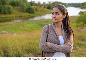 Young beautiful Asian woman thinking in nature