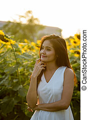 Young beautiful Asian woman thinking in the field of blooming su