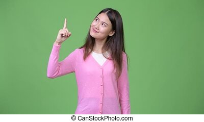 Young beautiful Asian woman thinking while pointing up