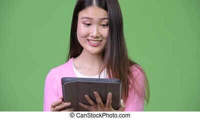 Young beautiful Asian woman using digital tablet