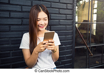 Young beautiful asian woman using her smart phone to listen, watch online music, and chatting with her friends