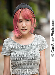 Young beautiful Asian woman with pink hair outdoors