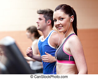 Young beautiful athletes with earphones exercising on a running machine in a fitness center