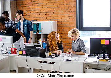 young beautiful auditor with red hair wearing glasses are examining office work