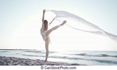 Young beautiful ballerina dancing ballet on seashore with ...