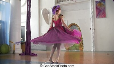 Young beautiful ballerina in purple dress performs dance in...