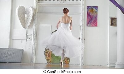 Young beautiful ballerina in white dress performs dance in...