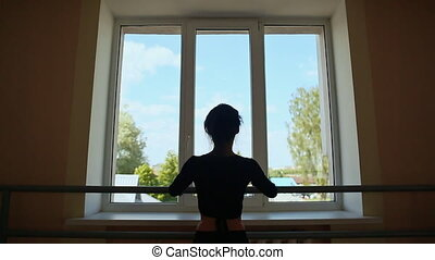 Young beautiful ballerina is dancing on the background of window