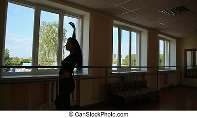 Young beautiful ballerina is dancing on the background of window.