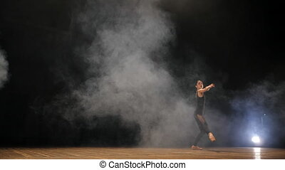 Young beautiful ballerina on smoke stage dancing modern ballet in the dark. Woman in black costume performs on scene. Sensual amazing dance. Art concept. Slow motion