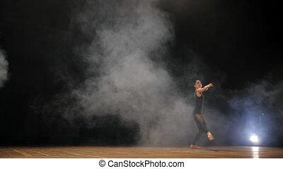 Young beautiful ballerina on smoke stage dancing modern...