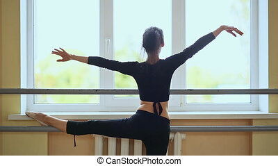 Young beautiful ballerina warming up in ballet class