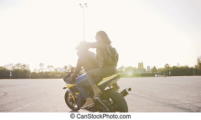 Young beautiful biker family at sunset riding on their motorcycle. Leather clothes, backpack, jeans