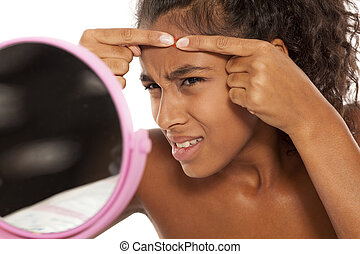 black woman squeezing pimples on her face - young beautiful...