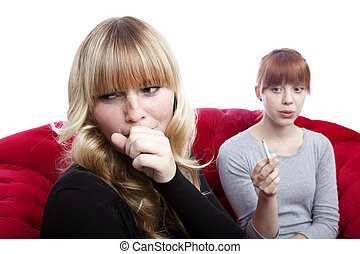 young beautiful blond and red haired girls on red sofa in ...