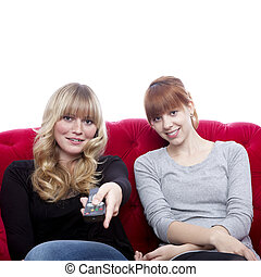 young beautiful blond and red haired girls on red sofa in...