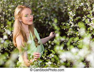 Young beautiful blond smiling woman in yellow dress standing in blooming cherry trees and looking at flower