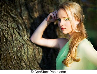 Young beautiful blond woman in yellow dress standing near tree trunk and looking aside on summer day