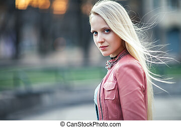Young beautiful blond woman portrait posing in city street on sunset