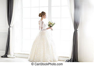 Young beautiful blond woman posing in a wedding dress