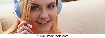 young beautiful blond woman sit on the sofa in livingroom hold laptop in arms listen to music