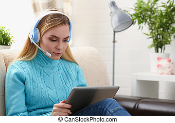 young beautiful blond woman sit on the sofa in livingroom hold tablet in arms listen to music sunny