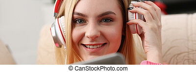 young beautiful blond woman sit on the sofa in livingroom hold tablet in arms listen to music